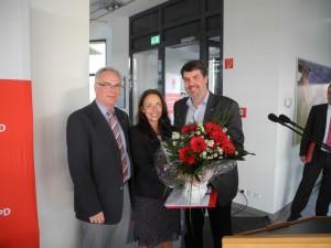 Michael Thews übergibt Yasmin Fahimi zusammen mit Rolf Möller als kleines Danke Schön neben einem Schrauberset noch ein Strauß Blumen